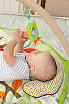 5 month old baby boy closeup on back reaching up to grasping dangled toy hanging from toy bar