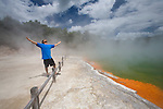 A tourist stands in the hot steam of the brilliantly coloured Champagne Pool at the geothermal site, Wai-O-Tapu Thermal Wonderland, near Rotorua on the North Island of New Zealand.