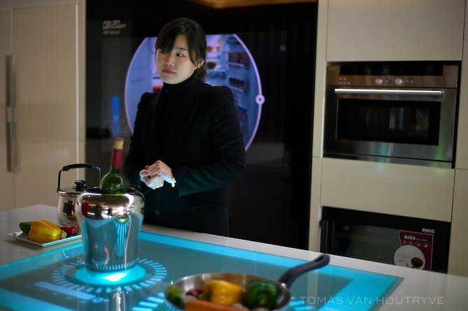 A woman demonstrates a kitchen in a model home equipped with the latest high-tech gadgets including energy efficient appliances connected a smart grid, a refrigerator that tracks supplies and a touch control range  in Seoul, South Korea on Feb. 1, 2012. Newly built apartments in Korea often come equipped with a host of high-tech items to manage the home..