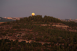 The Judean mountains, Israel. A view from Belmont Mount Tzuba of a full moon rising, Jerusalem is in the background<br />