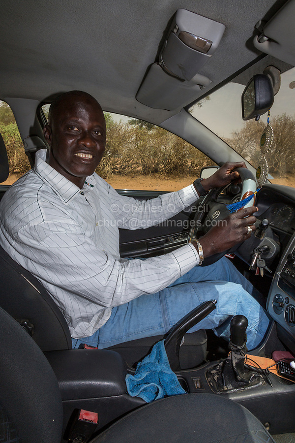 Senegal, Tivaouane.  Senegalese Driver, a Tijaniyya Muslim from Tivaouane, Wearing Western-style Clothing.  A protective Islamic talisman hangs under his rear-view mirror.