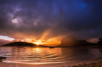 Last sunrays at sunset on Le Morne Brabant mountain with fishing boats on the Indian ocean, under a dramatic stormy sky in Mauritius Island, Africa