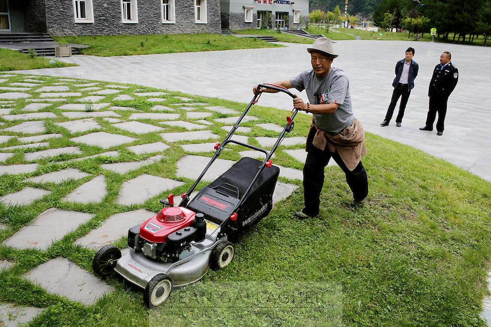 A man mowing grass in the Dagu Glacier park on the south-east edge of the Tibetan Plateau in Sichuan Province, western China.