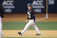 Nate Mondou (10) of the Wake Forest Demon Deacons waits for the arrival of his teammates after hitting a walk-off single in the bottom of the 9th inning against the Missouri Tigers at Wake Forest Baseball Park on February 22, 2014 in Winston-Salem, North Carolina.  The Demon Deacons defeated the Tigers 1-0.  (Brian Westerholt/Four Seam Images)