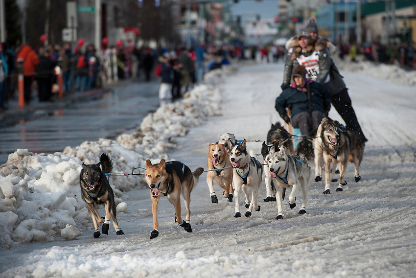 Matt Failor of Willow and his team round the corner of Fourth Avenue and Cordova Street at the ceremonial start of the 43rd Iditarod dog sled race in downtown Anchorage. 79 mushers made their way 11 miles through the slushy streets of Anchorage in unseasonably warm weather and early rain. This year's official re-start will begin in Fairbanks because of poor trail conditions in Southcentral Alaska.