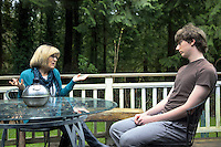 USA. Washington state. Fall City. ReStart Internet Addiction Recovery program at Heavensfield Retreat Center. Rosanne Sherlock (L) and Josh (R) sit outside on the balcony. Rosanne Sherlock is the daytime resident superviser. Josh is 20 years old and has dropped out of university because he was an highly addictive online video gamer on internet. ReStart is an unique intensive onsite program which offers to participants an opportunity to stay in a retreat center designed to promote insight and renewal, disconnect from digital distractions, and engage in coaching and mentoring while building a blue print for change. The three to six-month reStart program, the first of this kind in the United States, works to help men over 18, suffering from problematic internet, video game, social media and technology use by teaching positive and sustainable lifestyle change in a serene, rural environment surrounded by nature. 10.12.2014 © 2014 Didier Ruef