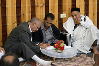 Tripoli, Libya - Preparing Wedding Contract.  Father of the bride signs after sheikh finalizes terms.  Groom's uncle observes after signing earlier.  Uncle wears a holi, the traditional wrap-around garment for men.
