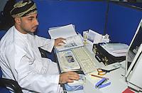 Muscat, Oman, Arabian Peninsula, Middle East - Omani Computer Worker, Bahwan Cybertek.  He wears the traditional Omani robe, a dishdasha, and headdress, the msarr or massar.