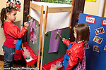 Education preschool 4-5 year olds two girls painting at nearby easels one shorter or taller than the other art activity