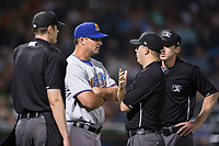 Durham Bulls manager Jared Sandberg (22) argues a call with first base umpire Brian Peterson as umpires Eric Gillam (left) and Alex Tosi look on during the game against the Charlotte Knights at BB&T BallPark on May 15, 2017 in Charlotte, North Carolina. The Knights defeated the Bulls 6-4.  (Brian Westerholt/Four Seam Images)