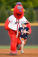 """A young fan races around the bases against the Winston-Salem Dash mascot """"Bolt"""" between innings at Wake Forest Baseball Stadium August 30, 2009 in Winston-Salem, North Carolina. (Photo by Brian Westerholt / Four Seam Images)"""