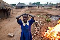 A Ugandan school girl passing a crop burn enroute to school in Madi Opei, Uganda.