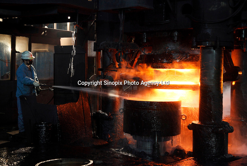 Workers operate on the old assembly line that was built in the 1960s to make train carriage wheels at Ma Steel in Maanshan, China. With an additional plant that opened last year, Ma Steel is the world's largest producer of train carriage wheels with an annual capacity of 1.1 million units. .29 Dec 2008.