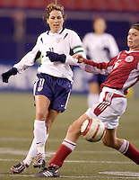 """USA's Julie Foudy passes the ball past the defense of Louise Hansen of Denmark. The US Women's National Team tied the Denmark Women's National Team 1 to 1 during game 8 of the 10 game the """"Fan Celebration Tour"""" at Giant's Stadium, East Rutherford, NJ, on Wednesday, November 3, 2004.."""