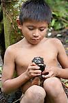 A Machiguenga boy holds a black-mantled tamarin, Manú National Park, Peru.