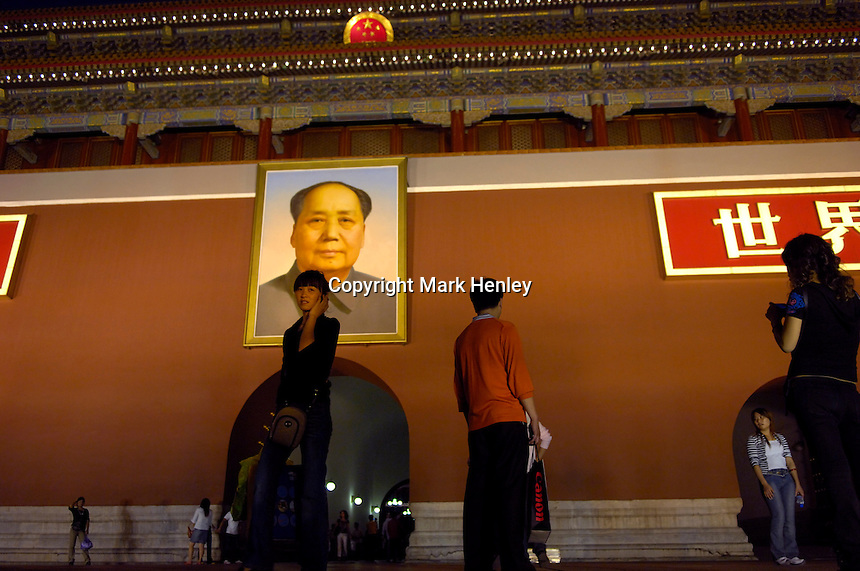 Young woman is using her mobile phone in front of Tiananmen Gate, under Mao portrait..21 Sep 2006