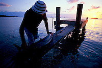 Garifuna man prepares to filet and gut fresh caught barracuda on dock as sun sets, Roatan, Honduras