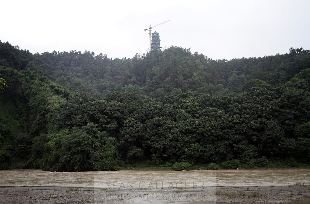 """A temple stands on a hill overlooking one of the main channels of the Dujiangyan Irrigation System. The system is regarded as an """"ancient Chinese engineering marvel."""" By naturally channeling water from the Min River during times of flood, the irrigation system served to protect the local area from flooding and provide water to the Chengdu basin. Sichuan Province. 2010"""