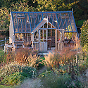 Greenhouse and garden in autumn evening light, late October. Planting includes Anthemis tinctoria 'Sauce Hollandaise', Calamagrostis brachytricha, Deschampsia cespitosa 'Golden Dew', Pennisetum alopecuroides 'Hameln', Scabiosa ochroleuca, and other perennials and grasses.