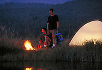 couple next to camp tent and camp fire at dusk. couple. Mt. Shasta California USA.