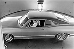 A woman holds out her hand to inspect her manicure she is wearing white sun glasses and on a car ferry. Galveston Texas USA 1969