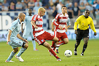 Andrew Jacobson (4) FC Dallas midfielder watched by Sporting KC defender Aurellien Collin... Sporting Kansas City defeated FC Dallas 2-1 at LIVESTRONG Sporting Park, Kansas City, Kansas.