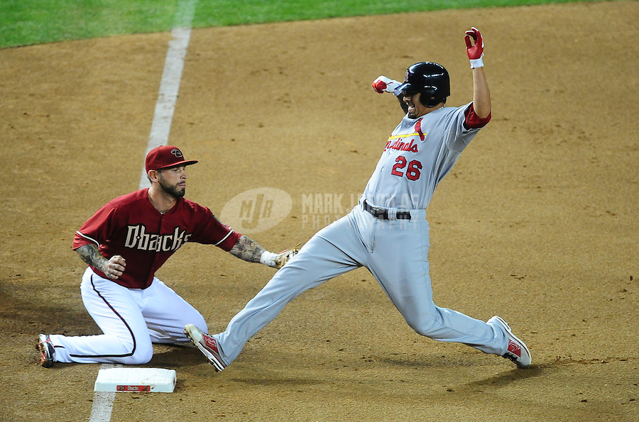 May 9, 2012; Phoenix, AZ, USA; St. Louis Cardinals pitcher Kyle Lohse (right) beats the tag by Arizona Diamondbacks third baseman Ryan Roberts in the fifth inning at Chase Field. Mandatory Credit: Mark J. Rebilas-
