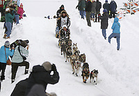 Saturday, March 3, 2012  Anna Berrington, her Idit-A-Rider, her handler and her dog team head down Cordova Hill during the Ceremonial Start of Iditarod 2012 in Anchorage, Alaska.