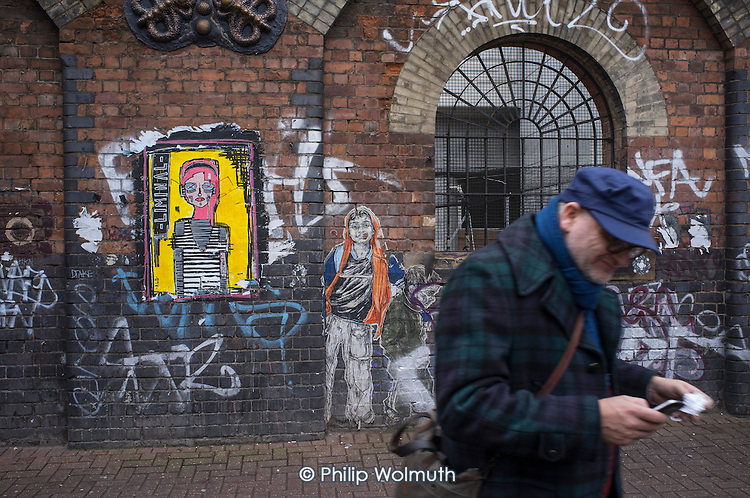 Wall art and passer-by in Shoreditch, London.