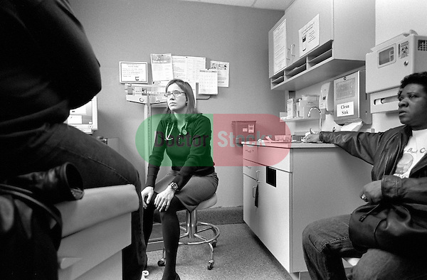 Young seated female internal medicine resident physician listening to middle age African-American female patient on examination table in examination room, patient accompanied by middle-age African-American friend