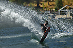 Water Skier leans way back to throw a wall of water.