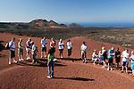 Spain, Canary Island, Lanzarote, near Yaiza: Parque Nacional de Timanfaya (Timanfaya National Park) - Islote de Hilario - tourists sampling hot volcanic gravel   Spanien, Kanarische Inseln, Lanzarote, bei Yaiza: Islote de Hilario im Timanfaya Nationalpark (Parque Nacional de Timanfaya), um die unterirdische, vulkanische Hitze zu demonstrieren gibt ein Parkranger jedem Besucher etwas heissen Vulkansand in die Hand