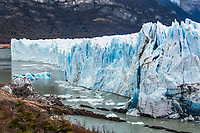 The jagged face of Perito Moreno Glacier and Lago Argentino in Los Glaciares National Park near El Calafate, Argentina.  A UNESCO World Heritage Site in the Patagonia region of South America.  Icebergs from calving ice from the glacier float in the lake.