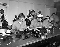 """Students working in the Naval School of Photography.  Class #4 specialize on movies.  Here students are splicing 35 m negative strips into proper sequence before the final printing on to a positive roll for projection.  In background are """"moviolas"""" or viewers on which a negative or positive roll may be run for study through a magnifying lens.  A light source behind the film and motor make the """"moviola"""" a miniature project room."""
