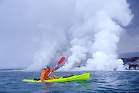 Man sea kayaking off the coast of the Big island with lava entering the sea