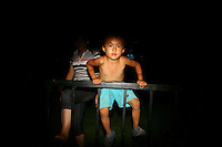 CHINA. Beijing. A young boy climbs a fence whilst watching the opening ceremony of the Beijing Summer Olympics. 2008