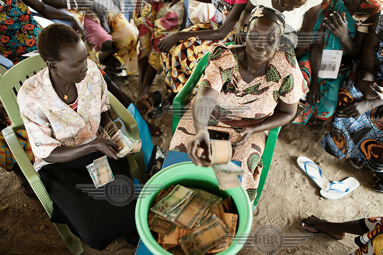 A woman puts bank notes into a basin during a meeting of a village saving group (VSLA).