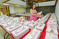 """COPY BY TOM BEDFORD<br /> Pictured: Member of staff Michelle Curry who has been trying on some of the dresses at the John Pye Auctions warehouse in Pyle, south Wales, UK.<br /> Re: A bride cried tears of joy after her missing wedding dress was found among a pile of 20,000 gowns in a warehouse.<br /> Meg Stamp, 27, paid £1,300 for the beautiful ivory lace dress but it  was seized by liquidators after a bridal company went bust.<br /> It was boxed up along with 20,000 others and due to be sold for a knock-down price at auction.<br /> But determined Meg banged on the auctioneer door saying: """"I want my dress back"""".<br /> Staff at John Pye auctioneers in Port Talbot spent three hours sifting through boxes until they finally found Meg's dream dress."""