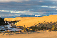 Two hikers on a ridge along the Ahnewetut Creek flows which through the Great Kobuk Sand Dunes in the Kobuk Valley National Park, Arctic, Alaska.