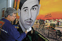 Faiez el Hazani a Palestinian artist draws a portrait of a Palestinian Martyr Nufak Al Harak killed in an operation at Kisufim junction. A former art painter Hazani had paint in his studio at the Beach Refugee Camp more than 100 portraits of Martyrs during the Intifadah who are seen in every corner in Gaza Strip. Photo by Quique Kierszenbaum