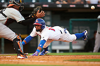 Buffalo Bisons shortstop Alexi Casilla (12) slides into home as catcher catcher Francisco Pena (29) waits for the throw during a game against the Norfolk Tides on July 18, 2016 at Coca-Cola Field in Buffalo, New York.  Norfolk defeated Buffalo 11-8.  (Mike Janes/Four Seam Images)