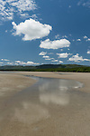 Cooya Beach, Port Douglas, Australia; cloud formations reflecting in the shallow water along the shoreline