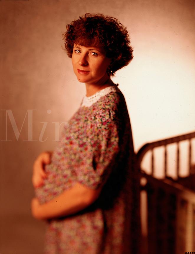 Portrait of pregnant woman next to crib.