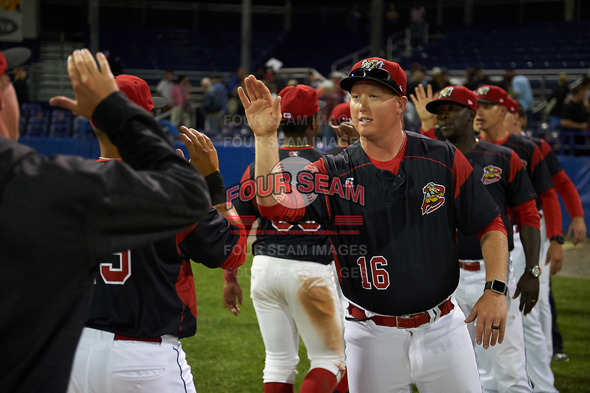 Batavia Muckdogs pitching coach Jason Erickson (16) high fives his team after a game against the Auburn Doubledays on June 19, 2017 at Dwyer Stadium in Batavia, New York.  Batavia defeated Auburn 8-2 in both teams opening game of the season.  (Mike Janes/Four Seam Images)