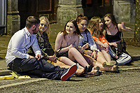Pictured: A group of young revellers sit on the pavement in Wind Street, Swansea. Monday 31 December 2018 and Tuesday 01 January 2019<br /> Re: New Year revellers in Wind Street, Swansea, Wales, UK