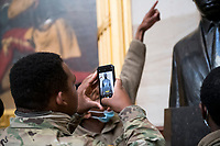 Members of the National Guard take photos of the statue of Martin Luther King Jr., in the Rotunda at the U.S. capitol, as the House of Representatives vote on H. Res. 24, Impeaching Donald John Trump, President of the United States, for high crimes and misdemeanors, at the U.S. Capitol in Washington, DC, Wednesday, January 13, 2021. Credit: Rod Lamkey / CNP /MediaPunch