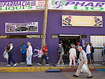 ALGODONES, MEXICO-MARCH 24: Tourists carry their purchases past the Farmacia liqui's, otherwise known as the Purple Pharmacy, March 24, 2005 in Algodones.  A third of the 40 million Americans on Medicare do not have prescription drug plans to help offset the costs of medications.©Radhika Chalasani