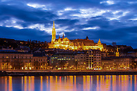 Famous Matthias Church in Buda castle, lit up under a cloudy twilight sky, with city light reflections on the Danube River, Budapest Hungary