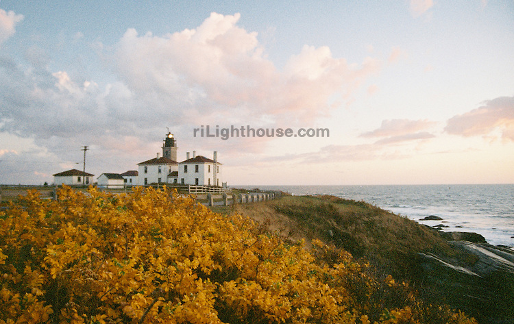 The setting sun gives a firey color to the autumn leaves at Beavertail Light.