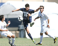 Gabe Padilla #25 of Georgetown University pulls in a high pass between Wesley Curtis #22 and Spencer Thompson #8 of Michigan State during an NCAA match at North Kehoe Field, Georgetown University on September 5 2010 in Washington D.C. Georgetown won 4-0.